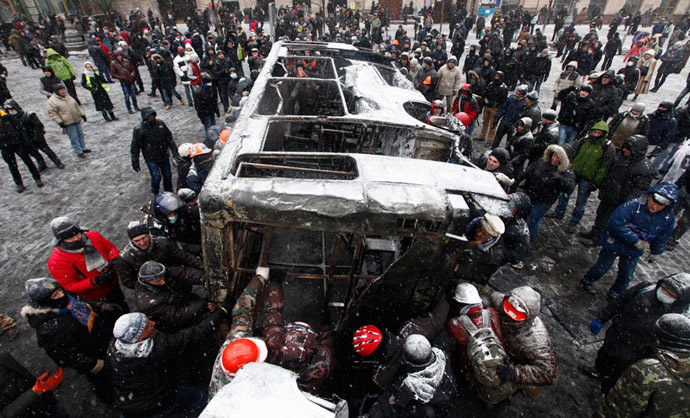 While more burnt vehicles are pushed over and used as makeshift barricades, an anti-government rally gathers in nearby Independence Square (Maidan Nezalezhnosti). (Reuters / Vasily Fedosenko)