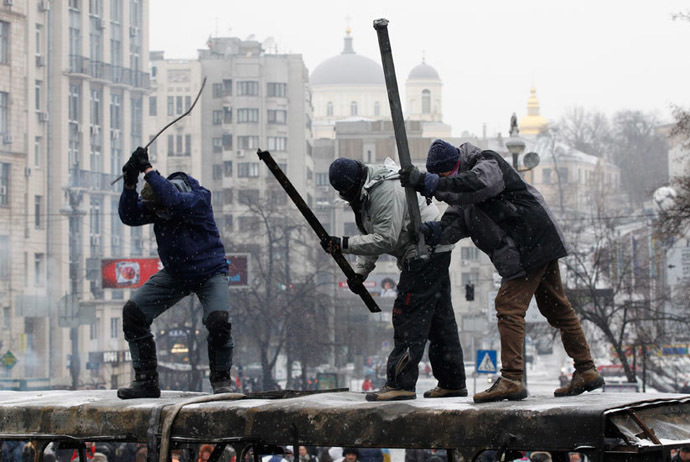 """Some protesters have been constantly drumming on burnt vehicles and empty barrels, with """"drums of war"""" going wild whenever clashes erupt. (Reuters / Vasily Fedosenko)"""