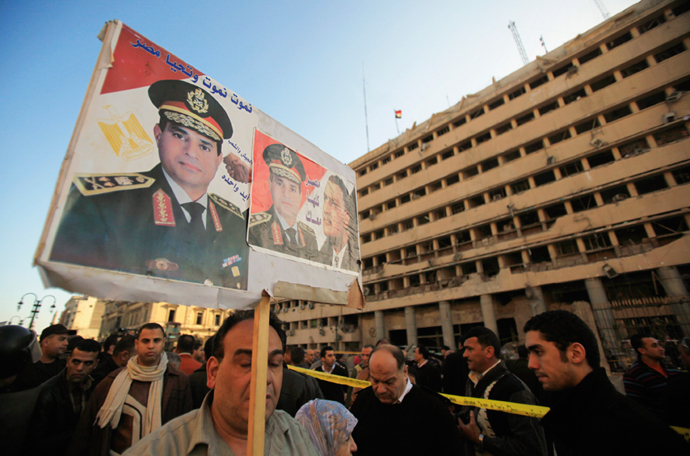 A supporter of Egypt's army chief General Abdel Fatah al-Sisi holds a poster in front of the damaged Cairo Security Directorate building, Cairo, January 24, 2014 (Reuters / Amr Abdallah Dalsh)