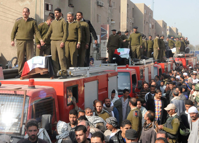 Egyptian police gather around the coffins during the funeral of five Egyptian policemen who were killed when masked gunmen on motorbikes opened fire on a checkpoint in the province of Beni Suef, 100 km (62 miles) south of Cairo, January 23, 2014 (Reuters / Al Youm Al Saabi Newspaper)