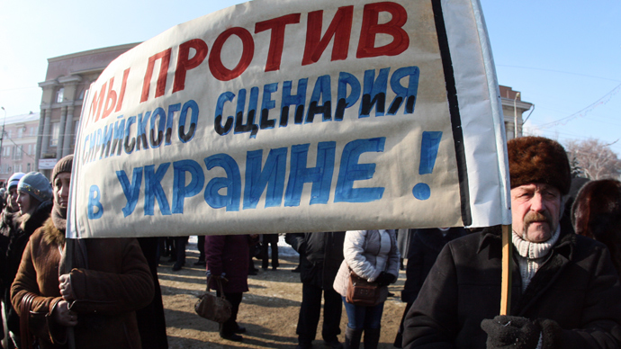 """People hold a sign reading """"""""We are against the Syrian scenario!"""" as they take part in a demonstration rally in support of the Ukrainian President, in the industrial city of Makeyevka, in the Donetsk industrial region, on January 25, 2014 (AFP Photo / Alexander Khudoteplov)"""