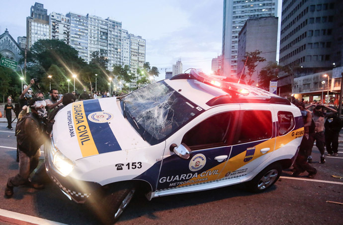 "A civil guard car is attacked by demonstrators during the ""Nao Vai Ter Copa"" (You are not going to have Cup) protest along Consolacao Street, in Sao Paulo, Brazil, on January 25, 2014. (AFP Photo/Miguel Schincariol)"