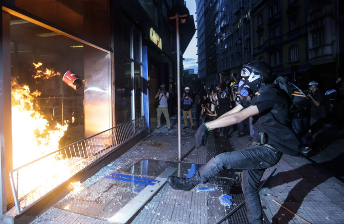 "Demonstrators attack a bank branch during the ""Nao Vai Ter Copa"" (You are not going to have Cup) protest along Consolacao Street, in Sao Paulo, Brazil, on January 25, 2014. (AFP Photo/Miguel Schincariol)"