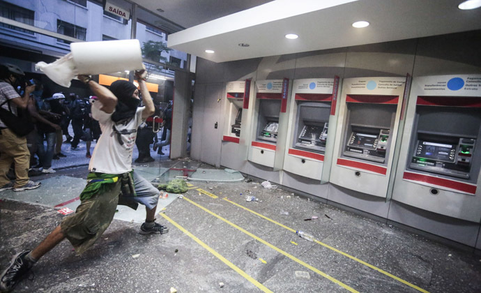 "A demonstrator attacks a bank branch during the ""Nao Vai Ter Copa"" (You are not going to have Cup) protest along Consolacao Street, in Sao Paulo, Brazil, on January 25, 2014. (AFP Photo/Miguel Schincariol)"