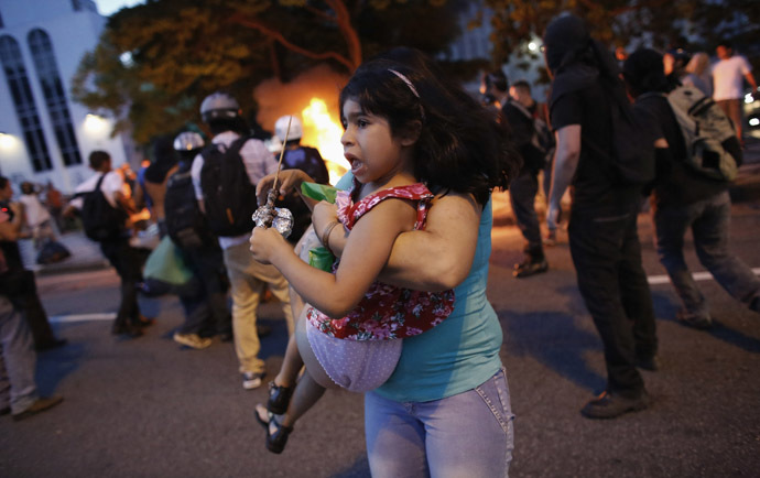 A woman carries her daughter away from their car, after it caught fire driving through a flaming barrier during a protest against the 2014 World Cup in Sao Paulo January 25, 2014. (Reuters/Nacho Doce)