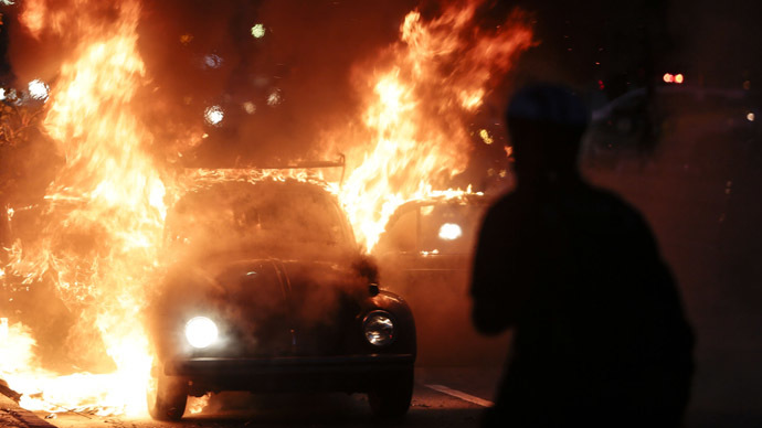"A car burns in flames during the ""Nao Vai Ter Copa"" (You are not going to have Cup) protest along Consolacao Street, in Sao Paulo, Brazil, on January 25, 2014. (AFP Photo/Miguel Schincariol)"