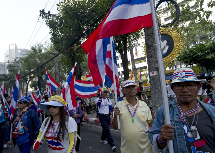 Thai anti-government protesters hold national flags as they parade to surrounded polling stations during a rally in Bangkok on January 26, 2014 (AFP Photo)