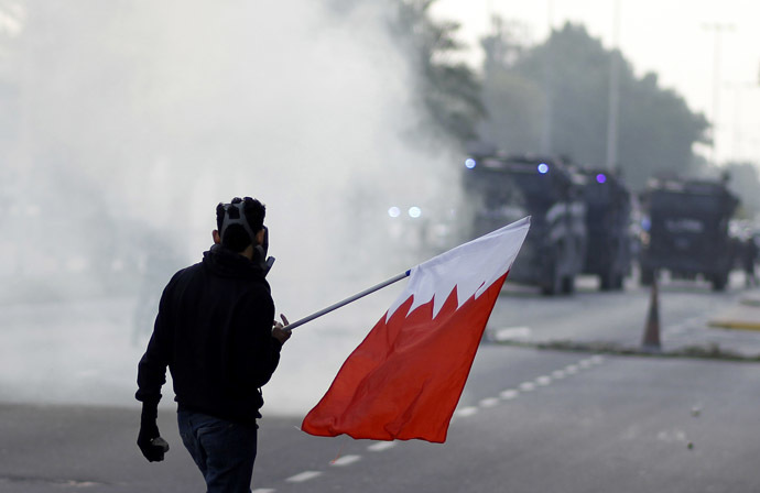 An anti-government protester holds a Bahraini flag during clashes with riot police after the funeral procession of Fadhel Abas Muslim in the village of Diraz, west of Manama, January 26, 2014. (Reuters/Hamad I Mohammed)