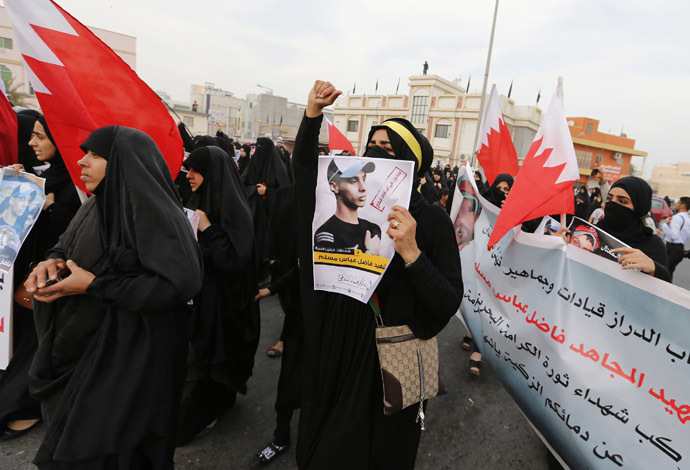 Anti-government protesters hold placards with images of Fadhel Abas Muslim, as they shout anti-government slogans while marching during his funeral in the village of Diraz, west of Manama, January 26, 2014. (Reuters/Hamad I Mohammed)