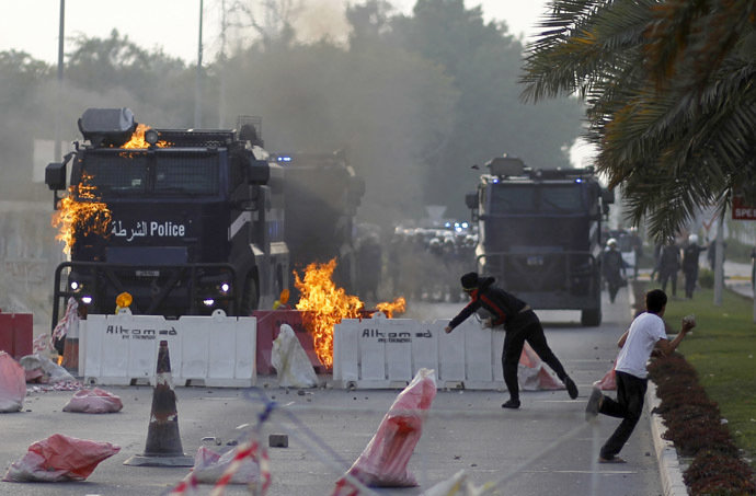 An anti-government protester throws a Molotov cocktail at a riot-police armored personnel carrier during clashes after the funeral procession of Fadhel Abas Muslim in the village of Diraz, west of Manama, January 26, 2014. (Reuters/Hamad I Mohammed)