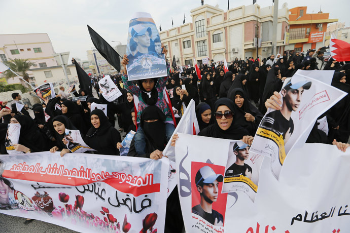 Anti-government protesters holding photos of Fadhel Abas Muslim, shout anti-government slogans as they march during his funeral in the village of Diraz west of Manama, January 26, 2014. (Reuters/Hamad I Mohammed)