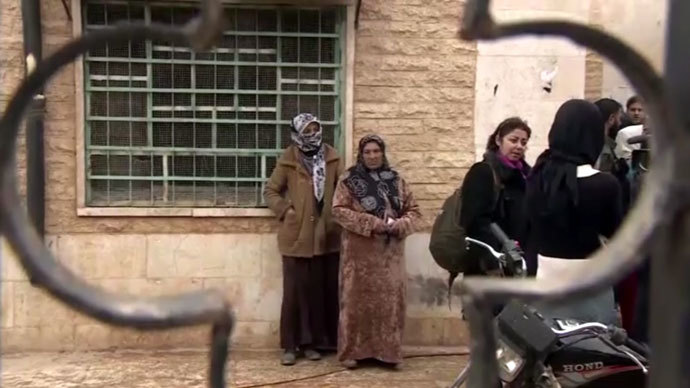 Refugees returning to a village just outside Aleppo, after the Syrian army took control. Screenshot from RT video