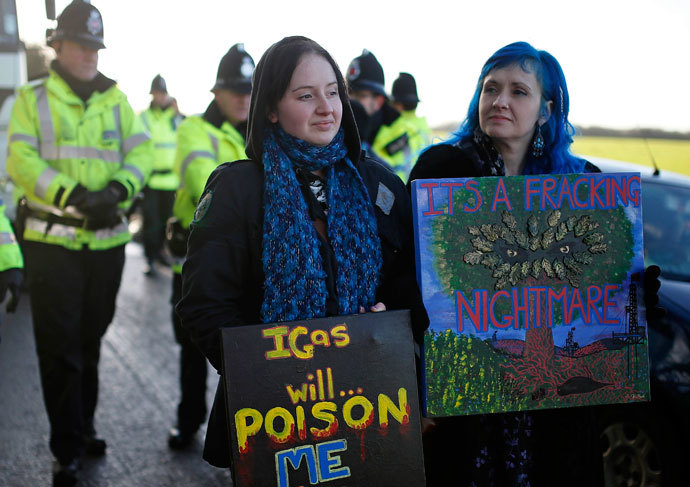 Demonstrators hold placards in front of a police cordon outside the entrance to the IGas Energy exploratory gas drilling site at Barton Moss near Manchester in northern England January 13, 2014. (Reuters / Phil Noble)