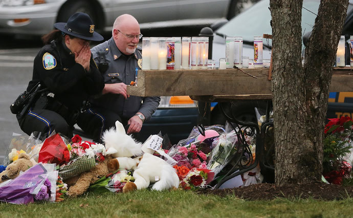Newtown Police officers pay their respects at a makeshift memorial outside St. Rose of Lima Roman Catholic Church during the first day of Sunday services following the mass shooting at Sandy Hook Elementary School on December 16, 2012 in Newtown, Connecticut.(AFP Photo / Mario Tama)