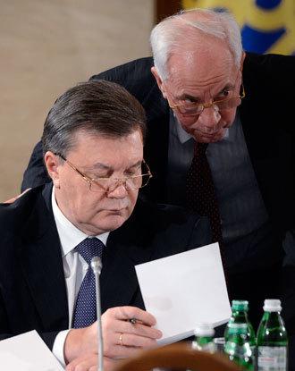 Ukraine's President Viktor Yanukovich (L) speaks with Prime Minister Nikolay Azarov.(Reuters / Andrew Kravchenko)