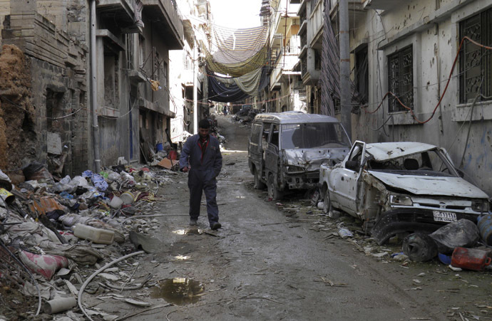 A man walks along a street past damaged buildings and vehicles in the besieged area of Homs January 28, 2014. (Reuters/Thaer Al Khalidiya)