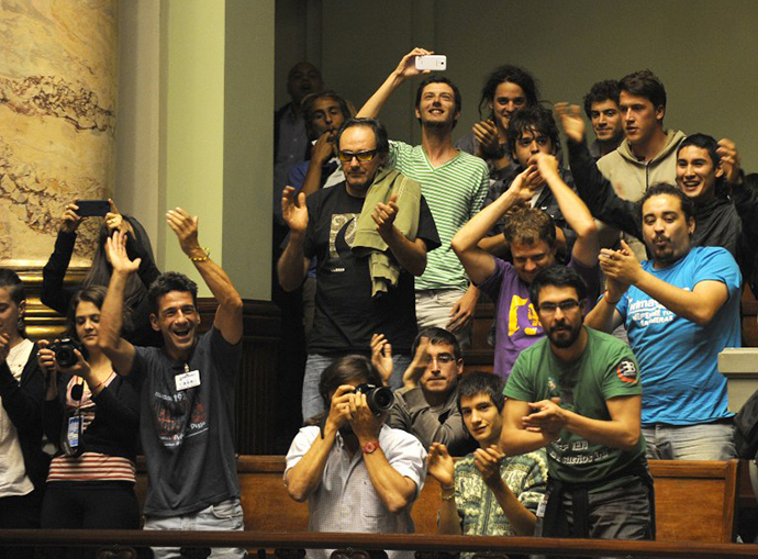 People celebrate after the Uruguayan senate approved a law legalizing marijuana in the Legislative Palace in Montevideo, on December 10, 2013. (AFP Photo / Miguel Rojo)