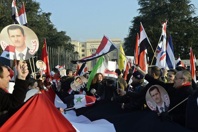 Pro-Syrian regime protesters, holding portraits of Syrian President Bashar al-Assad and waving Syrian flags take part to a demonstration in front of the United Nations headquarters in Geneva on January 31, 2014. (AFP Photo / Philippe Desmazes)