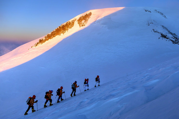 A handout picture taken during the Sochi 2014 Winter relay on October 22, 2013 and released by the Sochi 2014 Winter Olympics Organizing Committee, shows torchbearers carrying an Olympic torch to the Elbrus Mount in Russia's North Caucasus region. (AFP Photo/Sochi 2014 Winter Olympics Organizing Committee)