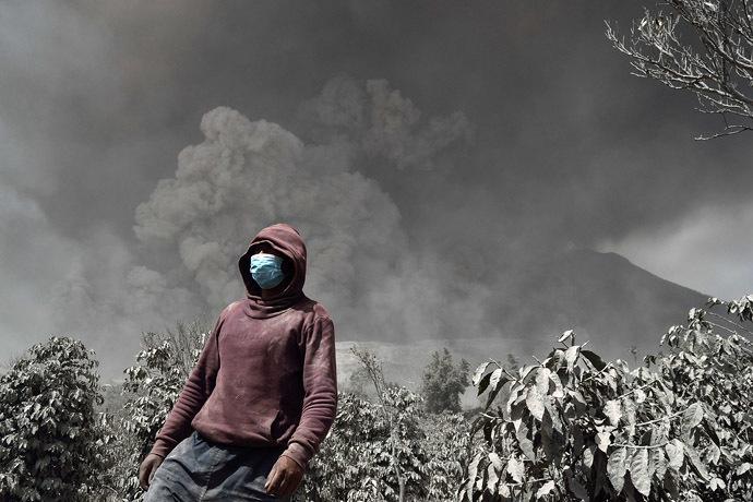 An Indonesian man wearing a mask stands against Sinabung volcano while it spews thick smoke and hot ash in Karo on January 16, 2014. (AFP Photo)