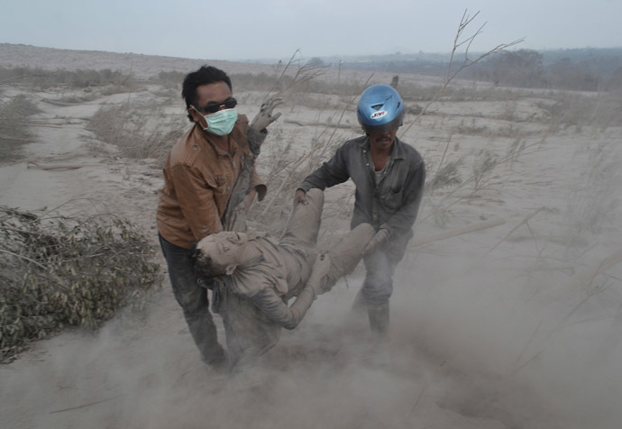 Indonesian residents rescue a victim following eruptions of Mount Sinabung in Karo district, North Sumatra province, on February 1, 2014. (AFP Photo)