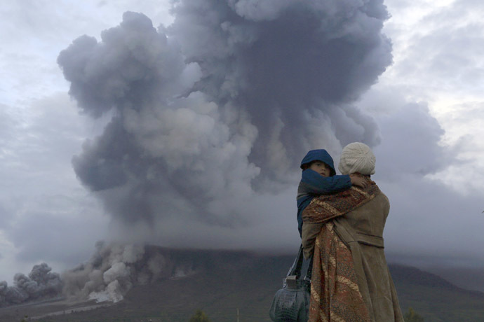 A mother holds her son as they watch the eruption of Mount Sinabung at Berastepu village in Karo district, Indonesia's North Sumatra province, January 10, 2014. (Reuters)