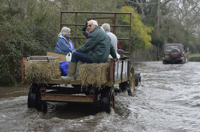 A tractor carries local residents along a flooded road from the village of Thorney on the Somerset Levels, near Langport in south west England January 30, 2014. (Reuters/Toby Melville)