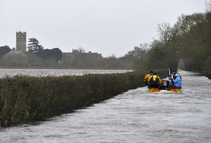 A boat operated by emergency services personnel carries local residents along a flooded road from the village of Muchelney on the Somerset Levels, near Langport in south west England January 31, 2014. (Reuters/Toby Melville)