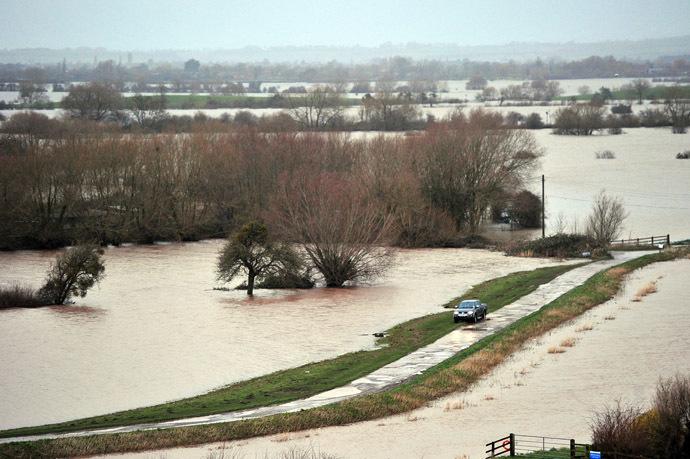 A car is driven on a road surrounded by flooded fields near Curload in Somerset, southwest England, on February 1, 2014. (AFP Photo/Carl Court)