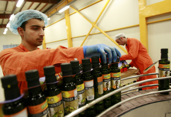 Workers pack bottles of olive oil at the Gaea extra virgin olive oil factory near the town of Agrinio about 350 km northwest of Athens (Reuters/John Kolesidis)