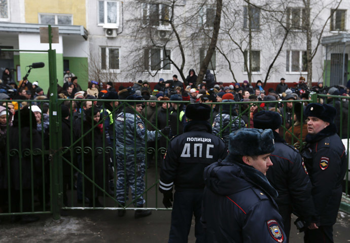 Interior Ministry members stand guard as bystanders and relatives of students gather behind a fence near a high school, where a student shot a teacher and a police officer dead and held more than 20 other students hostage, on the outskirts of Moscow, February 3, 2014. (Reuters/Maxim Shemetov)