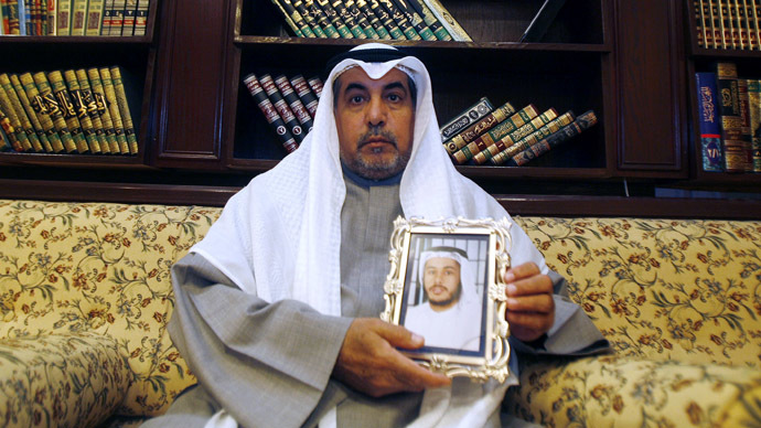 Khalid al-Odah, the father of Fawzi al-Odah, one of two Kuwaiti detainees still being held at Guantanamo Bay , holds his son's picture, at his home in the Qurtuba district of Kuwait City (AFP Photo)