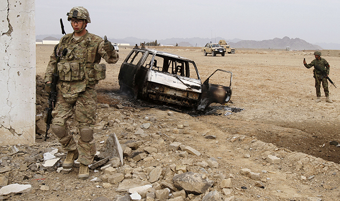 A U.S. soldier stands at the site of a suicide attack on a NATO base in Zhari, west of Kandahar province, January 20, 2014. (Reuters / Ahmad Nadeem)