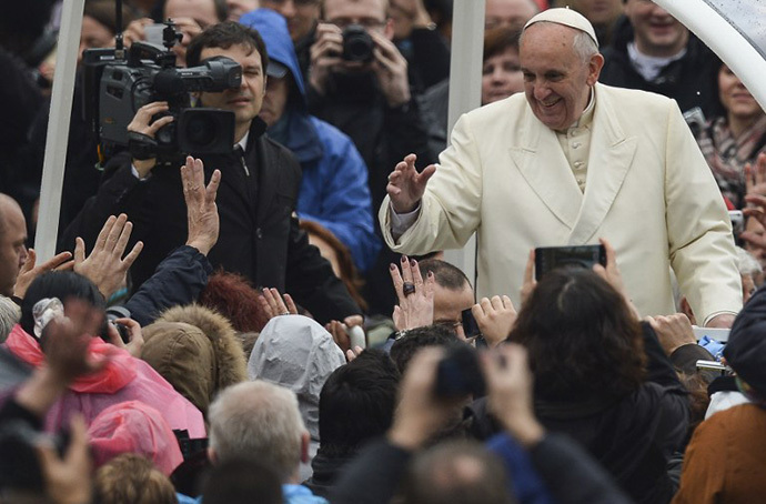 Pope Francis waves to pilgrims gathered at Saint Peter's square in the Vatican, upon his arrival to lead the general weekly audience on February 5, 2014. (AFP Photo / Vincenzo Pinto)