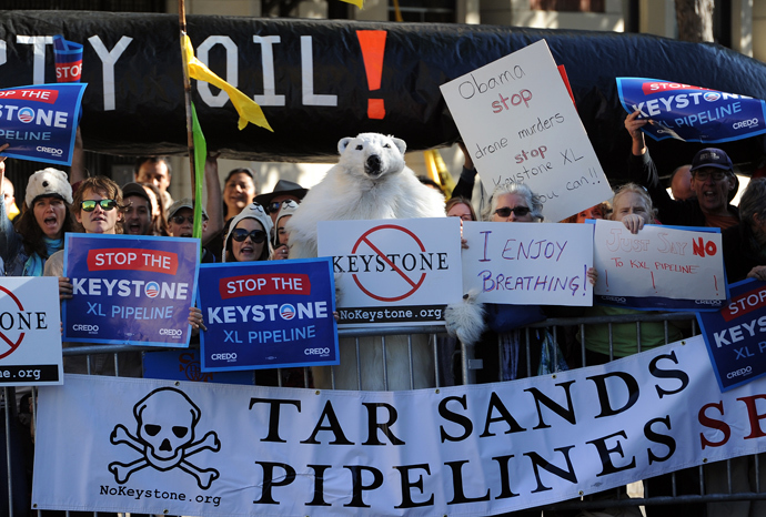 Protesters against the proposed Keystone XL pipeline hold placards across the street from where US President Barack Obama attends a Democratic Party fundraising event in San Francisco, California, on November 25, 2013. (AFP Photo / Jewel Samad)