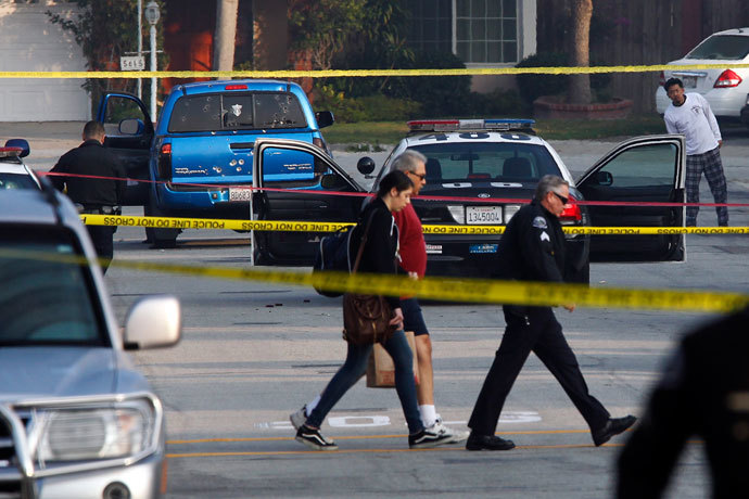 Bystanders are escorted from a crime scene while police detectives investigate a shooting incident involving a blue Toyota Tacoma pickup truck in Torrance, California, February 7, 2013.(Reuters / Patrick T. Fallon)