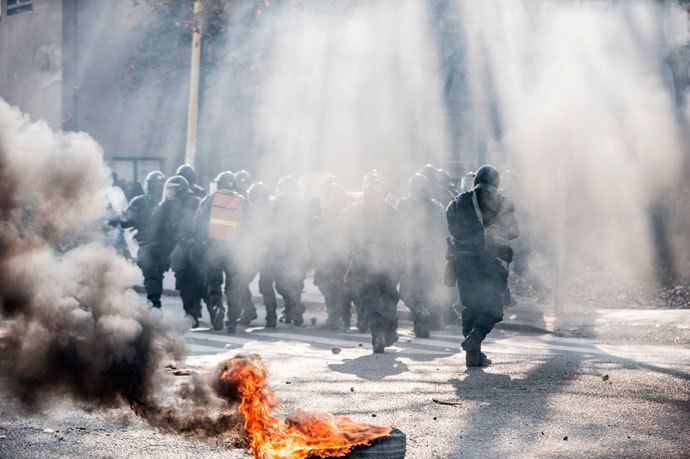 Smoke rises near the police as anti-government protesters hold a demonstration in Tuzla February 6, 2014.(Reuters / Edmond Ibrahimi)