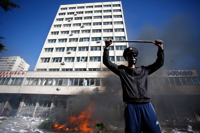 A protester stands near a fire set in front of a government building in Tuzla February 7, 2014. (Reuters / Dado Ruvic)