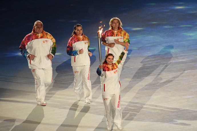 Russian gymnast and Olympian medalist Alina Kabaeva hold up the Olympic torch during the Opening Ceremony of the Sochi Winter Olympics at the Fisht Olympic Stadium on February 7, 2014 in Sochi.(AFP Photo / Damien Meyer)