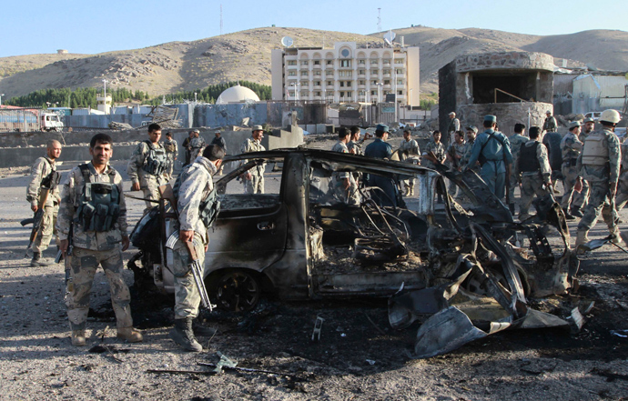 Afghan security forces inspect a damaged car, which was used during a suicide bomb attack, outside the U.S. consulate in Herat province September 13, 2013 (Reuters / Mohammad Shoib)