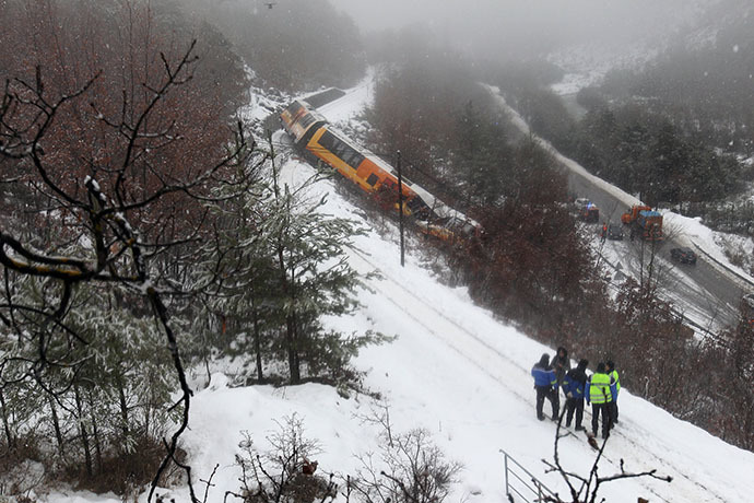 French gendarmes stand near the wreckage of a passenger train near Digne-les-Bains in the French Alps after it derailed on February 8, 2014. (AFP Photo / Jean-Christophe Magnenet)