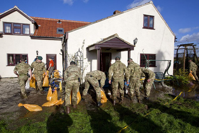 British Royal Marines help lay sandbags around a home threatened by floodwaters during flood relief operations in Moorland, some 19 Kms Northeast of Taunton on February 7, 2014. (AFP Photo / Justin Tallis)