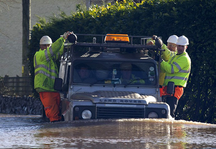 Environment agency workers take a ride on the side of a Land Rover as they travel through flood waters in Moorland, 19 Kms northeast of Taunton on February 7, 2014. (AFP Photo / Justin Tallis)