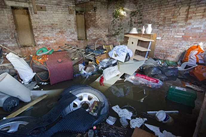 Belongings are seen, piled up in a outhouse which has been surrounded by flood water in Moorland, 19 Kms northeast of Taunton on February 7, 2014. (AFP Photo / Justin Tallis)