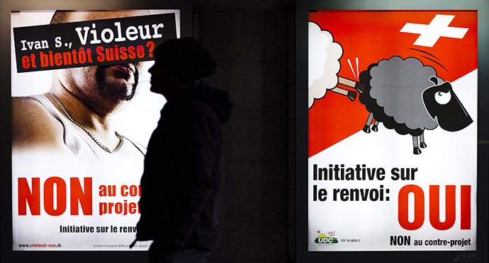 A man walks past posters of the Swiss People's Party (SVP) promoting the initiative to expel foreigners, in Lausanne, November 28, 2010. The posters read 'Ivan S., rapist and soon to be Swiss ?' and 'Yes to the initiative to expel foreigners'. (Reuters / Valentin Flauraud)