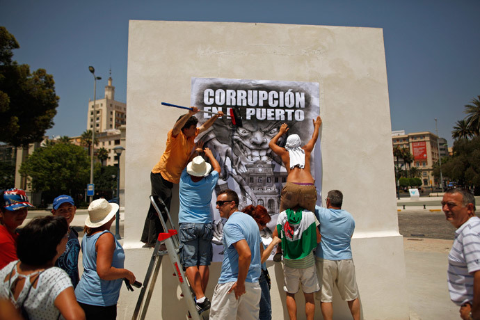 "Protesters and members of the Andalusian Union of Workers (SAT) place a banner reading ""Corruption at the port"" on the wall of a monument at Malaga's port during a demonstration against Spain's unemployment and the corruption in Malaga, southern Spain (Reuters / Jon Nazca)"