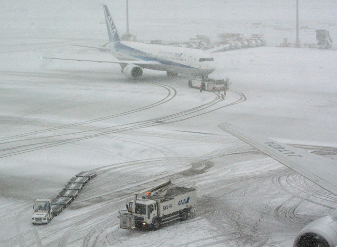 A jetliner of Japan's All Nippon Airways (ANA) taxis at Tokyo's Haneda airport covered by the snow on February 8, 2014 (AFP Photo / Kazuhiro Nogi)