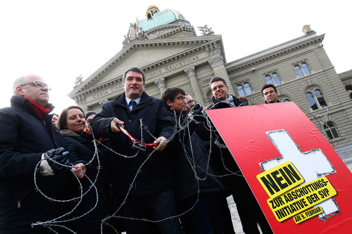 Parliament members and President of the Swiss Socalist Party SPS Christian Levrat (C) cuts a barbed wire fence on the Federal Square during a campaign in Bern January 29, 2014. (Reuters / Ruben Sprich)