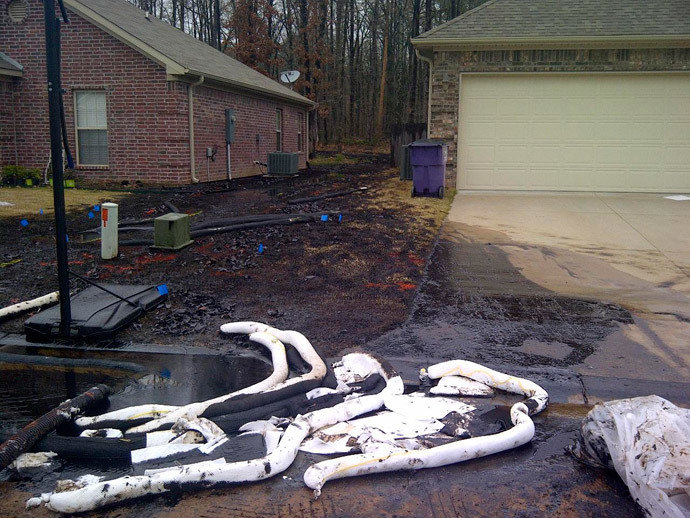 Spilt oil from Exxon pipeline runs between homes in North Woods Subdivision in Mayflower, Arkansas in this March 31, 2013 photo released to Reuters on April 11, 2013.(Reuters /Handout)