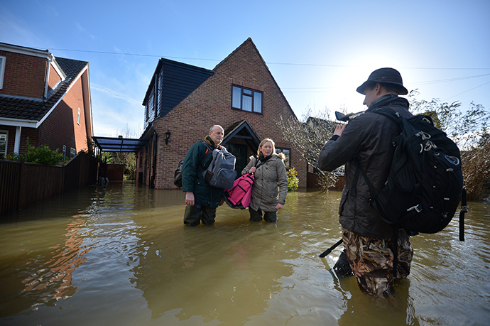 Residents speak to a TV journalist in a flooded street in the village of Wraysbury in Berkshire, South East England, on February 10, 2014. (AFP Photo / Ben Stansall)
